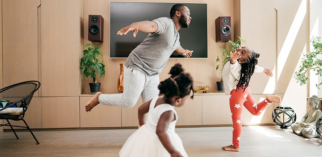 A man and two kids dancing in their living room.