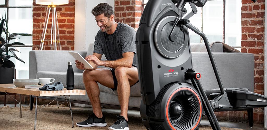 A man sitting next to a Bowflex Max Trainer