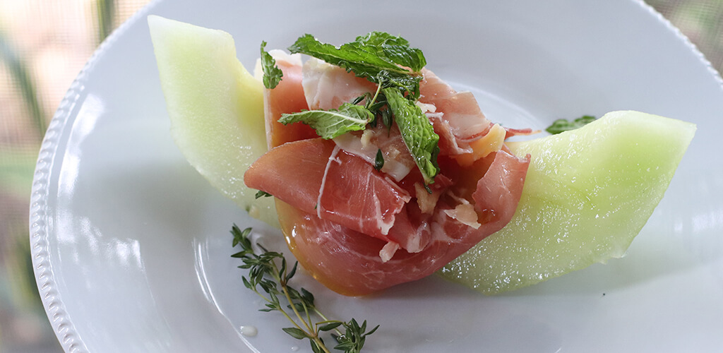 Prosciutto, parmesan, honeydew appetizer on a serving plate.