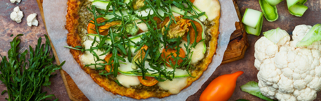 Pizza with cauliflower crust on a table with a head of cauliflower.