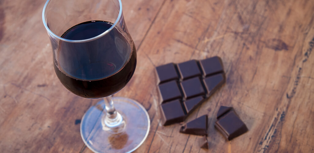 Dark chocolat next to a glass of red wine.