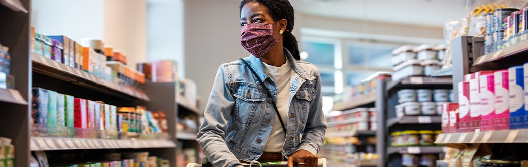 A person with a mask on grocery shopping.
