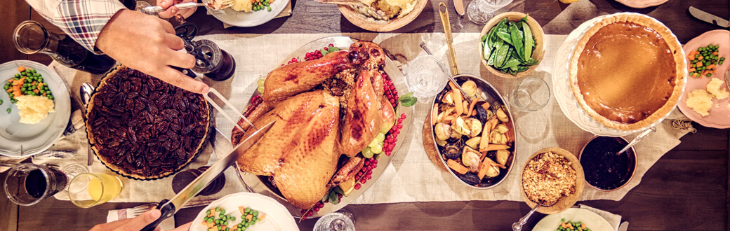 A dining room table with traditional Thanksgiving dishes on it.
