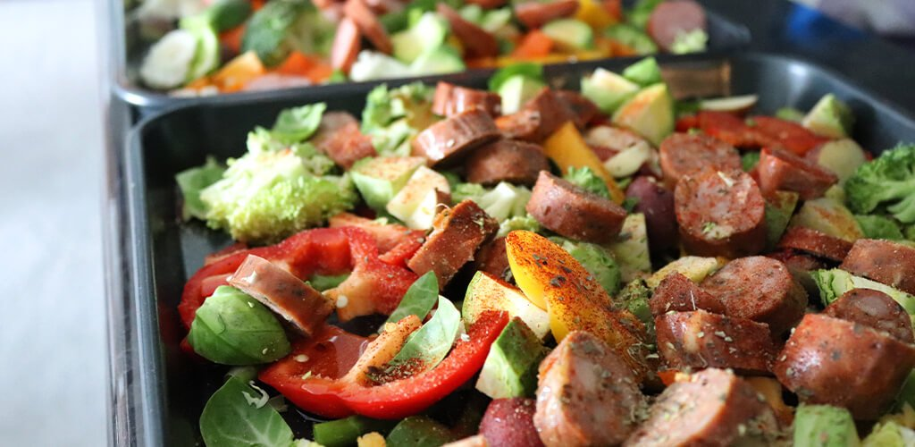 Assorted vegetables and sausage on a roasting pan.
