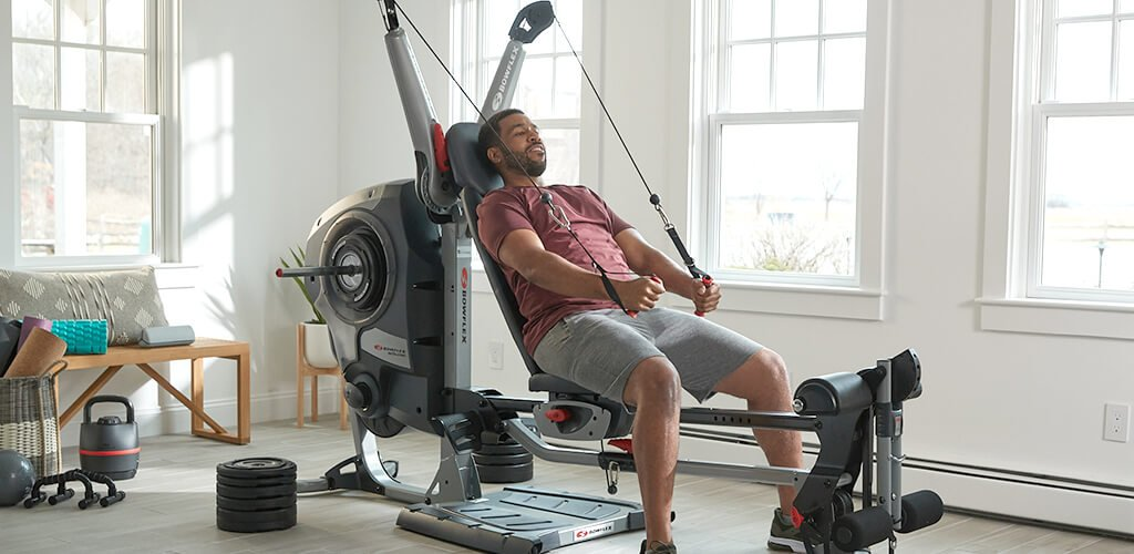 A man working out on a Revolution Home Gym.