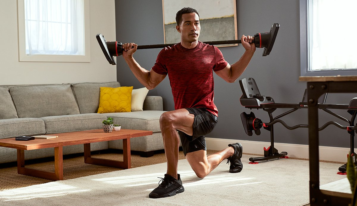 Man doing a barbell lunge in his living room