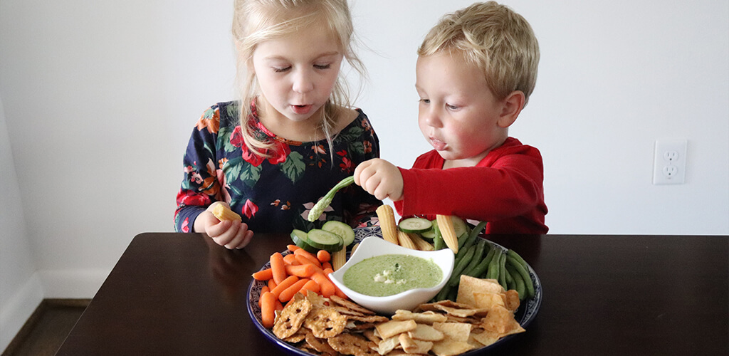 Two kids eating veggies and greek dip