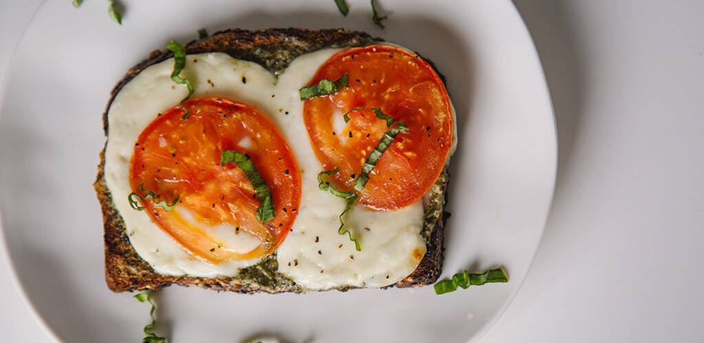Tomato, Pesto, And Fresh Mozzarella Open-Faced Grilled Cheese sandwich on a plate.