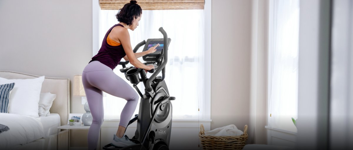 A woman working out on a Max Trainer compact elliptical in her bedroom.