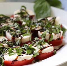 Caprese salad on a white plate.
