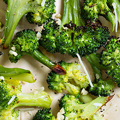 Closeup of roasted broccoli florets topped with Parmesan cheese.