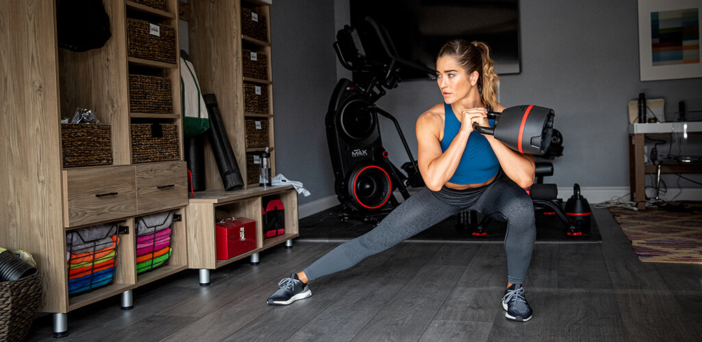 A woman peforming a side lunge with a bowflex kettlebell.