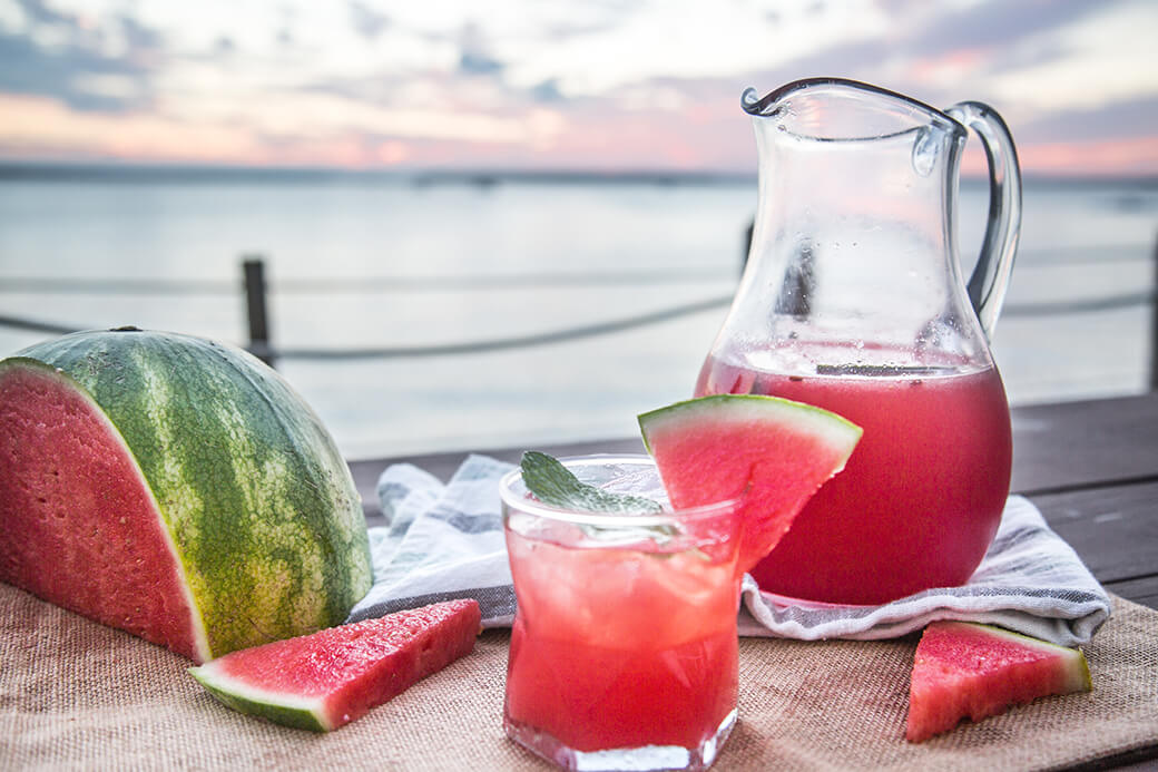 A glass filled with watermelon mojito mocktail. Garnished with mint and watermelon.