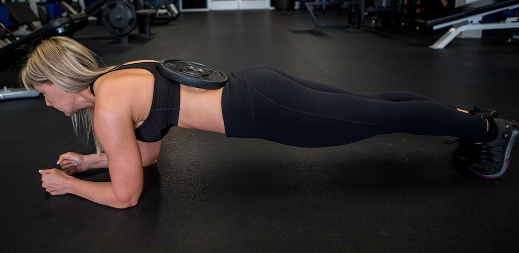 Lisa Traugott performing a weighted plank.