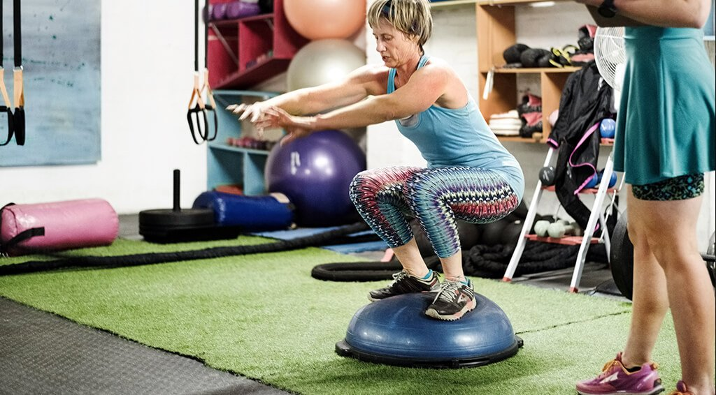 A woman balancing on a stability ball.