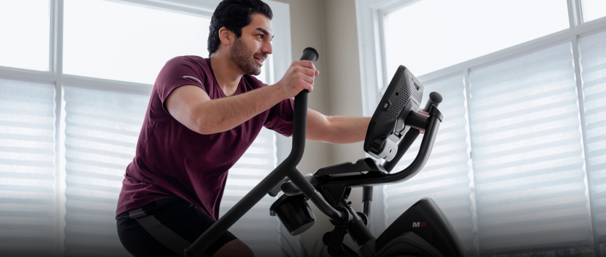 A man using a Max Trainer compact elliptial in a small apartment.