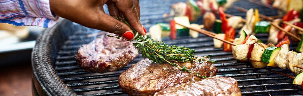 Meat and veggies on a BBQ grill.