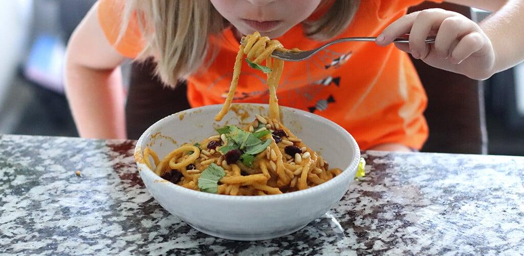 A child eating creamy pumpkin pasta