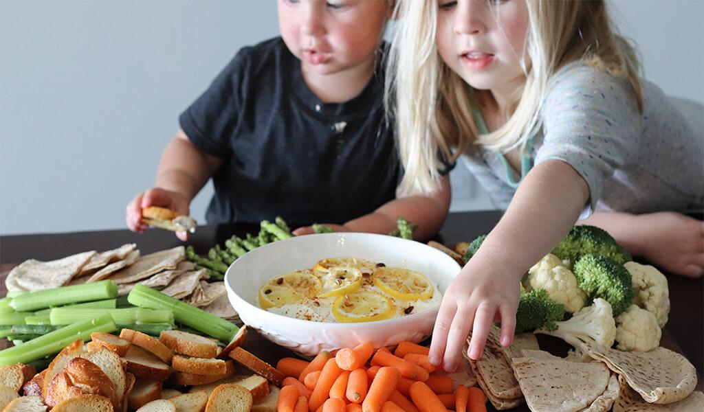 two kids eating lemon feta dip.