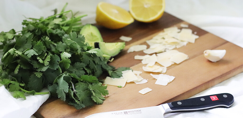 Cilantro, sliced avocado, lemon, and shaved parmesean cheese on a wood cutting board.
