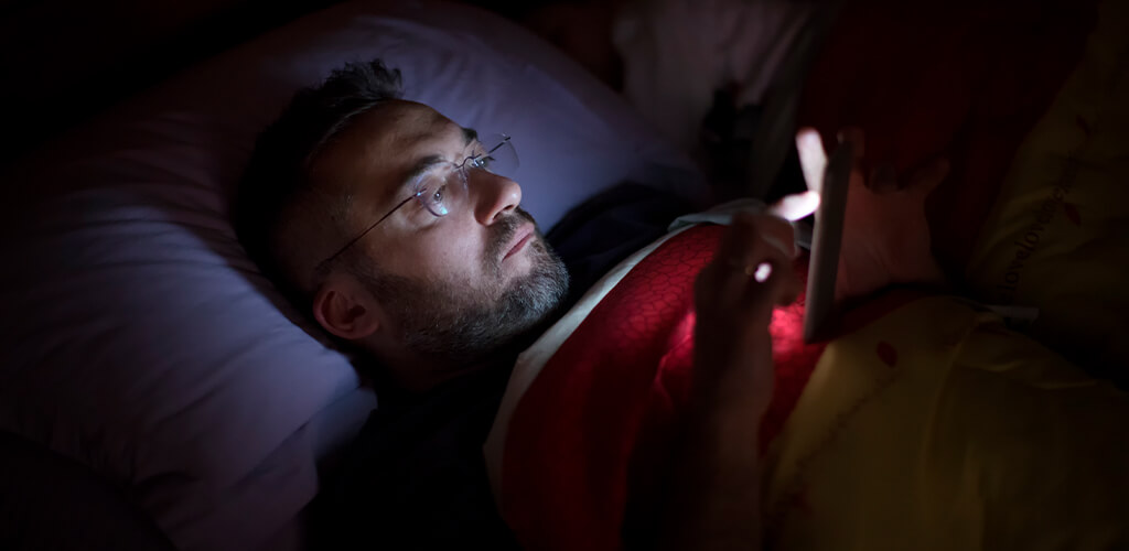 A man using his phone in bed.