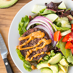 Close up image of burger salad. Hamburger patty on top of vegetables.