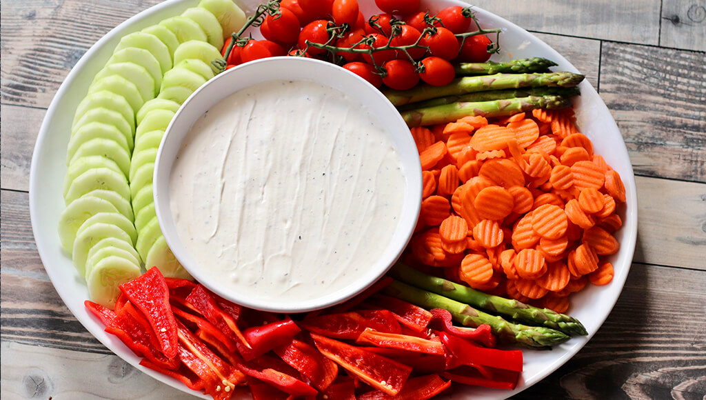 white truffle dip in a bowl surrounded by cut up veggies.