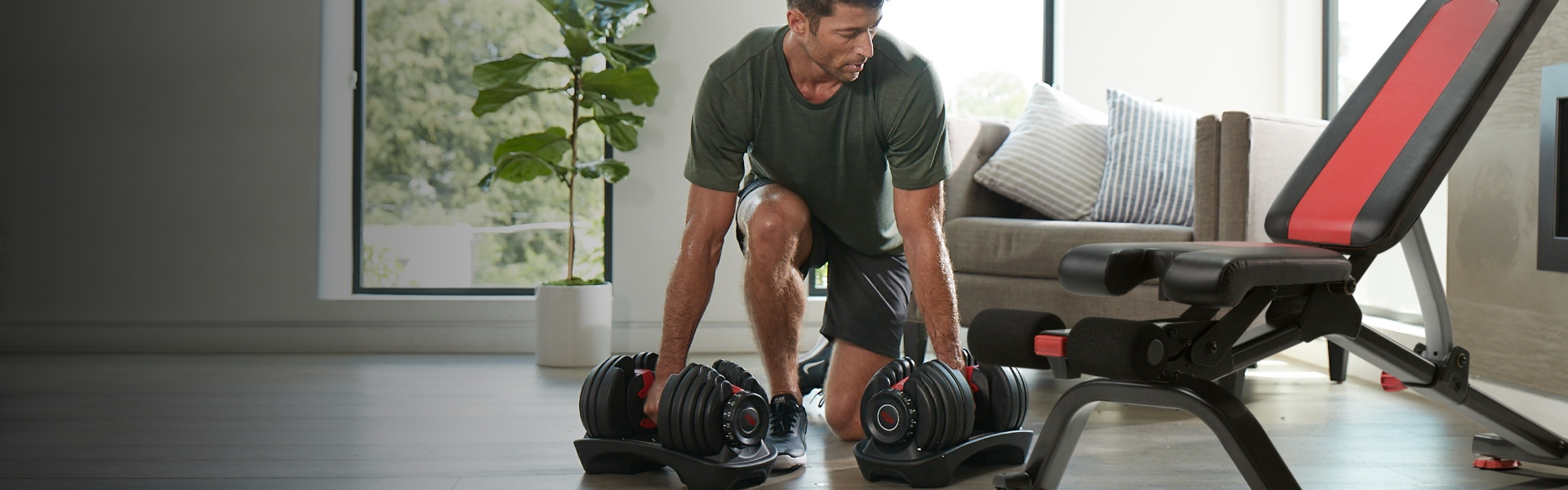 A man using Bowflex SelectTech 552 Dumbbells and a Bowflex Bench