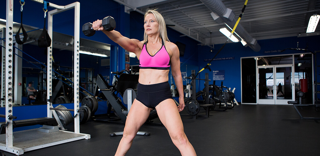 A fit woman performing a dumbbell swing in a squat position