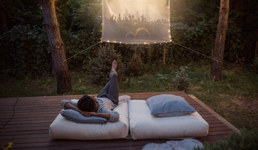 A person watching a movie in a backyard