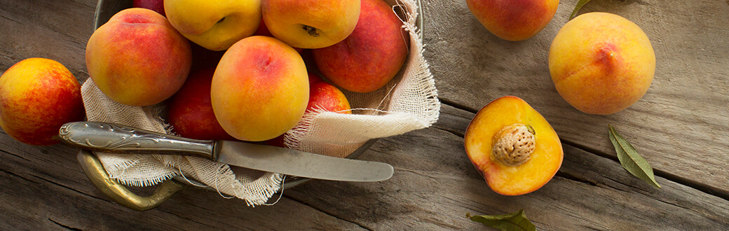 Peaches on a table being prepared for National Peach Month - Peach Crisp Recipe.