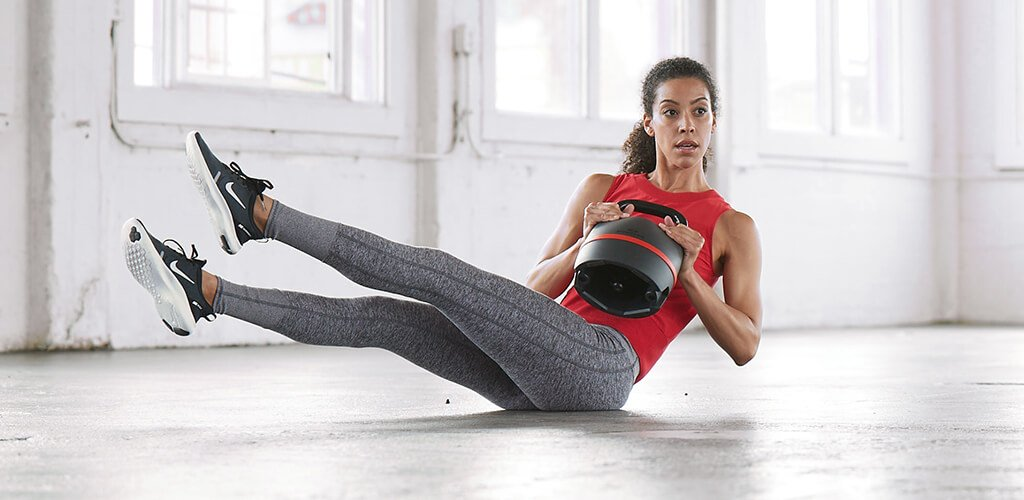 A fit woman using a SelectTech 840 Adjustable Kettlebell.